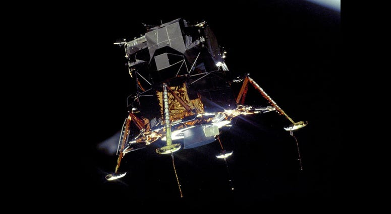 The Apollo 11 Lunar Module Eagle, in a landing configuration was photographed in lunar orbit from the Command and Service Module Columbia.