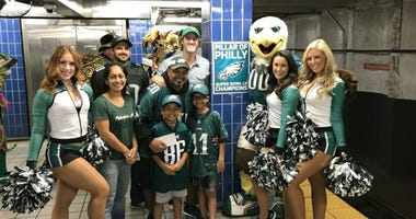 In this October 2018 photo, Jigar Desai poses with his family, friends and members of the Philadelphia Eagles Cheerleaders in front of the pillar he ran into earlier this year at Ellsworth Station on the Broad Street subway line in Philadelphia.