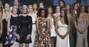 Former gymnast Sarah Klein, former Michigan State softball player Tiffany Thomas Lopez and gymnast Aly Raisman, from left in front, and others who suffered sexual abuse accept the Arthur Ashe Award for Courage at the ESPY Awards