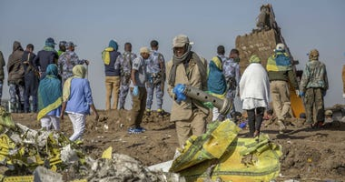 Workers gather at the scene of an Ethiopian Airlines flight crash near Bishoftu, or Debre Zeit, south of Addis Ababa, Ethiopia, Monday, March 11, 2019.