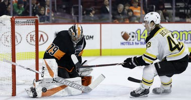 Philadelphia Flyers' Carter Hart, left, blocks a shot by Boston Bruins' Danton Heinen during the first period of an NHL hockey game, Wednesday, Jan. 16, 2019, in Philadelphia.