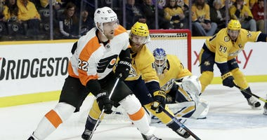 Philadelphia Flyers right wing Dale Weise (22) moves the puck as Nashville Predators defenseman Ryan Ellis (4) follows during the first period of an NHL hockey game Tuesday, Jan. 1, 2019, in Nashville, Tenn.