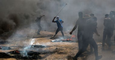 Palestinian protesters use slingshots to hurl stones at Israeli troops