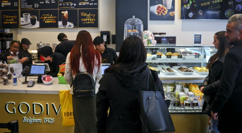 Customers wait in line for service at Godiva's new cafe in New York, Tuesday April 16, 2019.