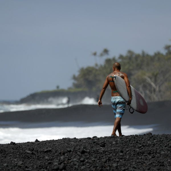 In this Tuesday, April 23, 2019 photo, a surfer walks on a newly formed black sand beach below Kilauea volcano near Kapoho, Hawaii