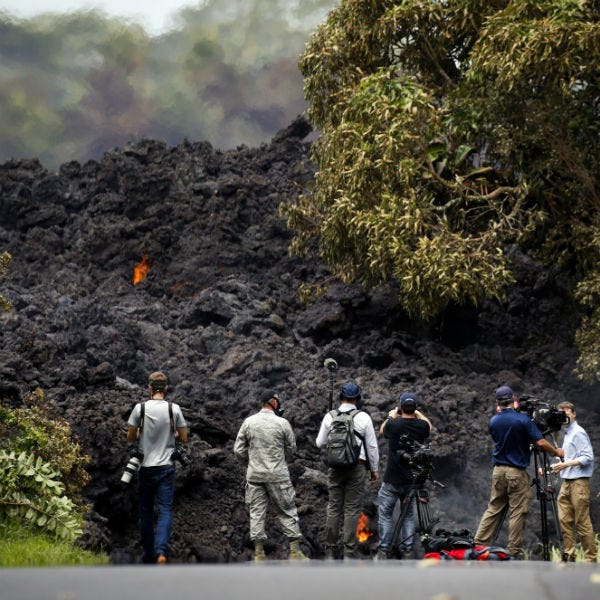 In this May 20, 2018 file photo, members of the media record a wall of lava entering the ocean near Pahoa, Hawaii.
