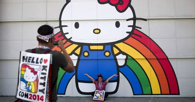 In this Oct. 30, 2014, file photo, Keith Nunez, left, takes pictures of his wife, Carolina, at the first-ever Hello Kitty fan convention, Hello Kitty Con, at the Geffen Contemporary at MOCA in Los Angeles.