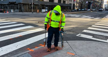 Errol Ray outside spraying paint in Center City on a frigid Monday afternoon.