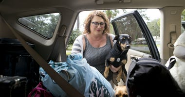 Julie Logsdon loads her dogs Tobias and Luna into her car in Panama City, Fla., as Hurricane Michael approaches on Tuesday, Oct. 9, 2018.