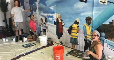 Local artists Brad Carney (left) and Melissa Mandel (right), along with student volunteers, paint a smaller version of the mural before they will paint the pedestrian and vehicular tunnels along Fifth Street under the Benjamin Franklin Bridge.