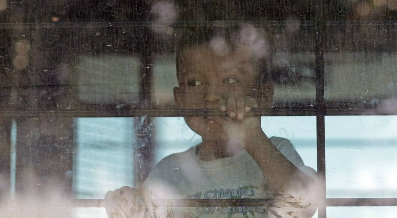 In this June 23, 2018, file photo, an immigrant child looks out from a U.S. Border Patrol bus leaving as protesters block the street outside the U.S. Border Patrol Central Processing Center in McAllen, Texas.