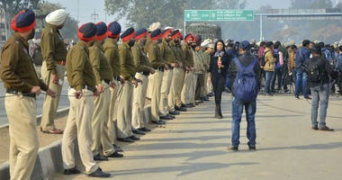 Indian policemen and media person wait for the return of Indian pilot at India Pakistan border at Wagah, 28 kilometers (17.5 miles) from Amritsar, India, Friday, March 1, 2019.