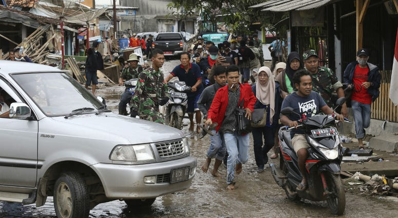 People run in panic on a street in Sumur village, Indonesia, Tuesday, Dec. 25, 2018.