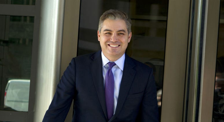 CNN's Jim Acosta walks out of the U.S. District Courthouse with a smile, Friday, Nov. 16, 2018, in Washington.