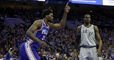 Philadelphia 76ers' Joel Embiid, left, celebrates after a dunk past San Antonio Spurs' LaMarcus Aldridge during the first half of an NBA basketball game, Wednesday, Jan. 23, 2019, in Philadelphia.