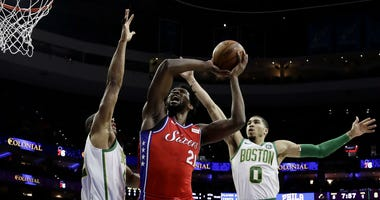 Philadelphia 76ers' Joel Embiid, center, goes up for a shot between Boston Celtics' Al Horford, left, and Jayson Tatum during the first half of an NBA basketball game, Tuesday, Feb. 12, 2019, in Philadelphia.