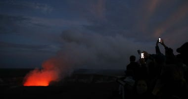 Visitors take pictures as Kilauea's summit crater glows red in Volcanoes National Park, Hawaii, Wednesday, May 9, 2018.