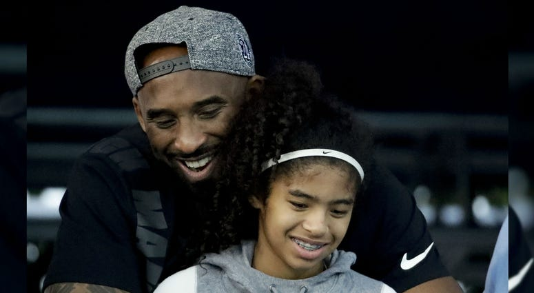 Former Los Angeles Laker Kobe Bryant and his daughter Gianna watch during the U.S. national championships swimming meet in Irvine, Calif., in 2018.