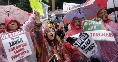 Teachers and supporters hold signs in the rain during a rally Monday, Jan. 14, 2019, in Los Angeles.