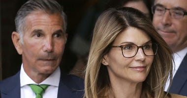 In this April 3, 2019 file photo, actress Lori Loughlin, front, and husband, clothing designer Mossimo Giannulli, left, depart federal court in Boston after facing charges in a nationwide college admissions bribery scandal.