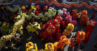 In the Tuesday, Feb. 5, 2019, photo, multiple dragon dances take part in Lunar New Year celebrations in the Chinatown area of Yangon, Myanmar.