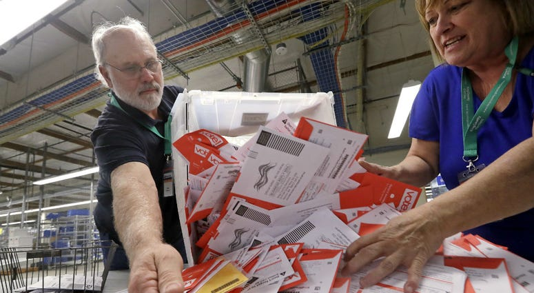 Election workers Mark Bezanson, left, and Julie Olson dump ballots collected earlier in the day from drop boxes onto a table for sorting at the King County Elections office, Monday, Nov. 5, 2018, in Renton, Wash.