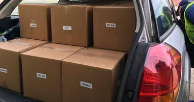 Volunteers stack boxes of pies in cars to deliver to distribution points throughout the city.