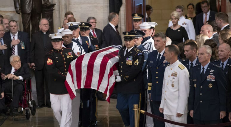The flag-draped casket bearing the remains of Sen. John McCain of Arizona, who lived and worked in Congress over four decades, is carried into the U.S. Capitol rotunda.