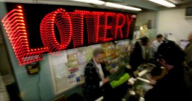 A woman sells Mega Millions lottery tickets