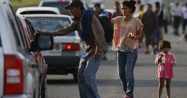 Central American migrants traveling with a U.S.-bound caravan beg for money from passing cars in Cordoba, Veracruz state, Mexico, Sunday, Nov. 4, 2018.