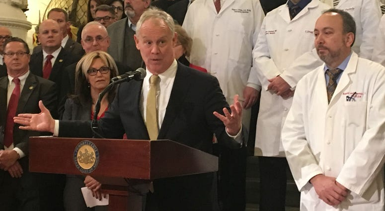 Flanked by doctors, Pa. House Speaker Mike Turzai speaks at the Capitol in Harrisburg.