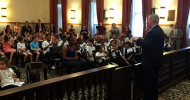 Elementary school students are shown at City Hall for a mock trial.