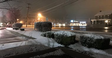Snow sticks to the grass and bushes, but the roads are clear by the five points intersection in Montgomeryville, Pa.