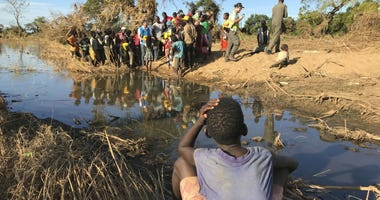 In this photo taken Saturday, April 6, 2019 a boy watches a demonstration of water filters in the remote village of Bopira, Mozambique.