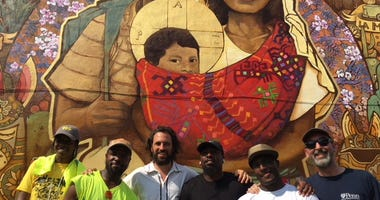 "Chilean artist Ian Pierce (third from left) and his crew worked in partnership with Mural Arts Philadelphia to conceive and create the ""Families Belong Together"" mural, displayed as a protest to the Trump administration's zero tolerance policy."
