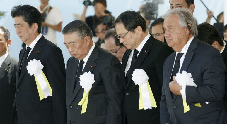 United Nations Secretary-General Antonio Guterres, right, and Japanese Prime Minister Shinzo Abe, left, offer a silent prayer during a ceremony at Nagasaki Peace Park in Nagasaki, southern Japan Thursday, Aug. 9, 2018.