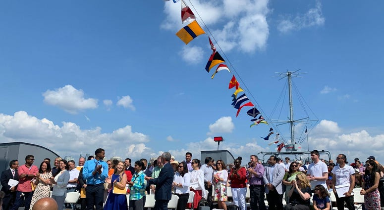 40 new Americans say the Oath of Allegiance at a Fourth of July naturalization ceremony aboard the Battleship New Jersey.