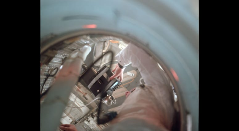 View up the tunnel towards the LM showing Neil holding the TV camera. Note how the small TV monitor has been taped to the camera body.