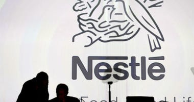 Nestle's directors speak in front of the Nestle's logo