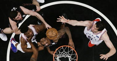 Philadelphia 76ers' Boban Marjanovic, right, shoots over Brooklyn Nets' Ed Davis, center, during the first half in Game 3 of a first-round NBA basketball playoff series Thursday, April 18, 2019, in New York. The 76ers won 131-115.