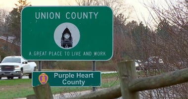 In this Tuesday, Feb. 27, 2019, image made from video vehicles make their way near a Union County sign, in Bladen County, N.C.