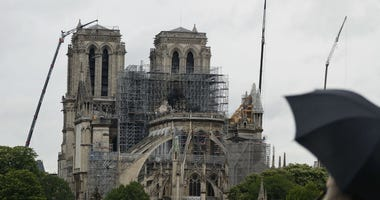 Cranes work at Notre Dame cathedral, in Paris, Thursday, April 25, 2019. French police scientists were starting to examine Notre Dame Cathedral on Thursday for the first time since last week's devastating fire.