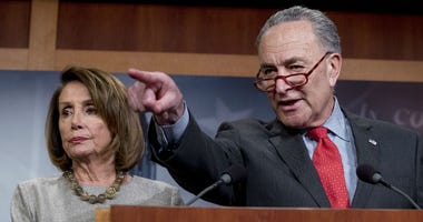 In this Jan. 25, 2019, file photo, Senate Minority Leader Sen. Chuck Schumer of N.Y., accompanied by Speaker Nancy Pelosi of Calif., left, calls on a reporter during a news conference on Capitol Hill in Washington.