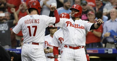 Philadelphia Phillies' Rhys Hoskins, left, and Jorge Alfaro, center, celebrate next to New York Yankees catcher Kyle Higashioka