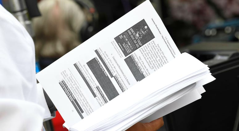 Television networks print out and read the released Mueller Report on the sidewalk outside of the Department of Justice.