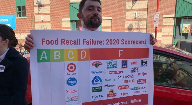 A man holds up a sign that has information on food recall failures by grocery stores.