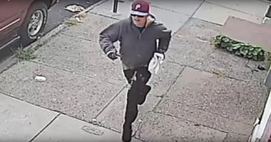 Robbery suspect wearing gloves, sunglasses and a burgundy Phillies cap.