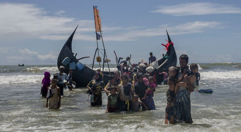 In this Sept. 14, 2017 file photo, a Rohingya man carries two children to shore in Shah Porir Dwip, Bangladesh, after they arrived on a boat from Myanmar.
