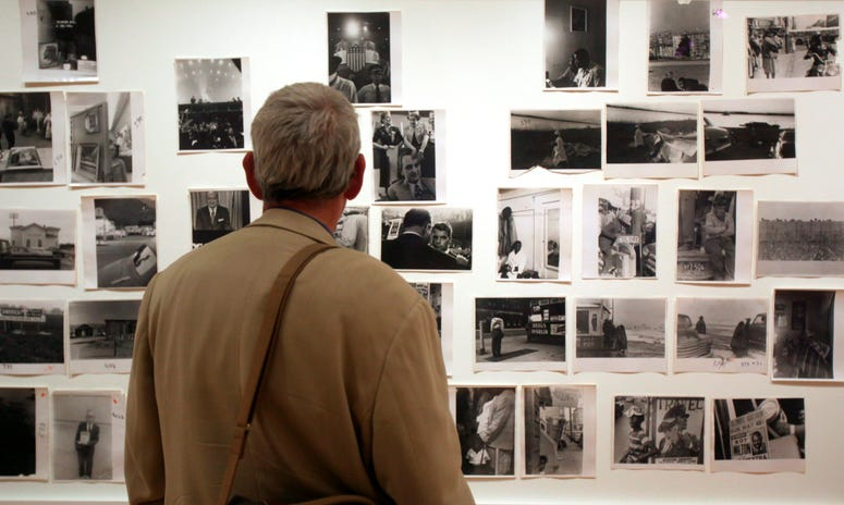 """A man looks at prints from the Looking In: Robert Frank's """"The Americans"""" exhibit at the Museum of Modern Art in San Francisco."""