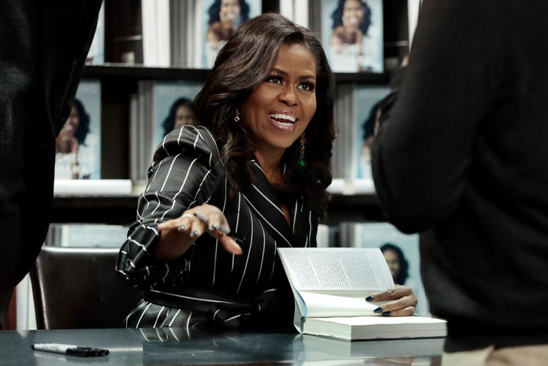"""Former first lady Michelle Obama signs books during an appearance for her book, """"Becoming,"""" in New York."""